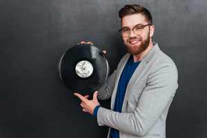 Smiling man with vynil in studio. looking at camera. isolated black background