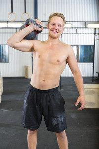 Smiling man without shirt lifting kettlebell at fitness gym