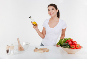 Smiling model by the table with food. Girl looking at camera