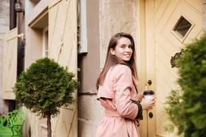 Smiling model in coat with coffee. stands sideways. near the door