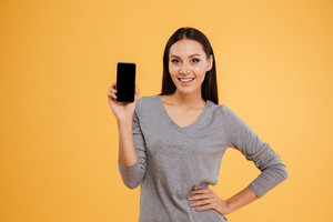 Smiling model with phone. isolated orange background