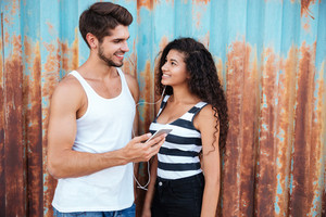 Smiling multiethnic young couple using earphones and listening to music from smartphone