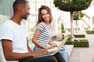 Smiling multiethnic young couple using laptop and cell phone outdoors