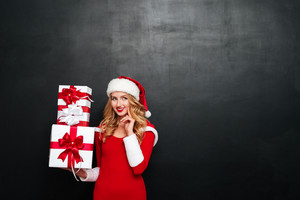 Smiling pensive young woman in santa claus hat holding gift boxes