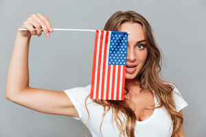 Smiling playful young woman covered her eye with flag of America over gray background