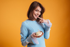 Smiling playful young woman standing and holding cake over yellow background
