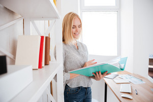 Smiling pretty busiess woman holding open folder with documents while standing at book shelf in office