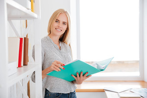 Smiling pretty busiess woman holding open folder with documents while standing at office and looking at camera