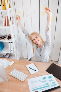 Smiling pretty business woman having a break and stretching hands while sitting on chair in office