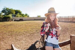 Smiling pretty redhead cowgirl using mobile phone while standing at ranch fence