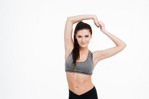 Smiling pretty sports woman stretching hands over white background