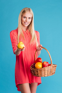 Smiling pretty woman holding straw basket with fruits isolated on a blue background