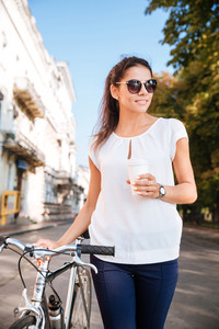 Smiling pretty woman in sunglasses walking with bicycle and takeaway coffee