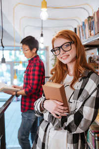 Smiling pretty young woman in glasses with book standing while man reading in library