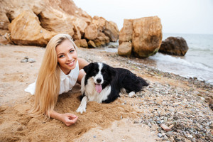 Smiling pretty young woman lying with dog on the beach