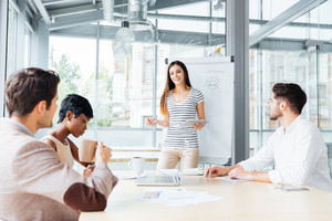 Smiling pretty young woman making presentation for business people in office