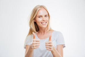 Smiling pretty young woman showing thumbs up isolated on the white background