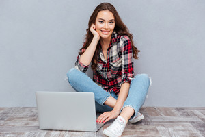 Smiling pretty young woman sitting and using laptop