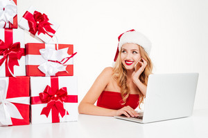 Smiling pretty young woman with present boxes in santa claus hat talking on mobile phone and using laptopx over white background