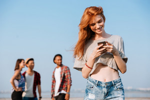 Smiling redhead young woman standing and using mobile phone near her friends outdoors