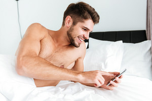 Smiling relaxed young man lying and using mobile phone in bed