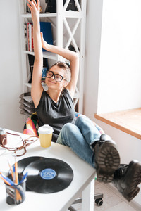 Smiling relaxed young woman in glasses sitting and stretching at the table at home
