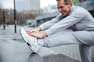 Smiling runner in gray sportswear and headphone warming up on the street. Stretching his legs. Side view