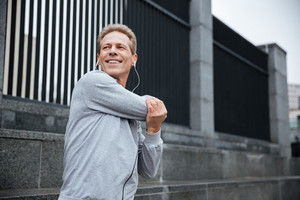 Smiling Runner in gray sportswear and heaphone warming up on the street. Side view