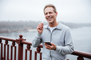 Smiling Runner in gray sportswear holding phone and listening to music on bridge