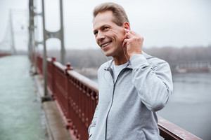 Smiling Runner in gray sportswear standing and listening to music on bridge