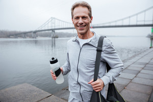 Smiling Runner in gray sportswear standing with water and bag near the river and looking at camera