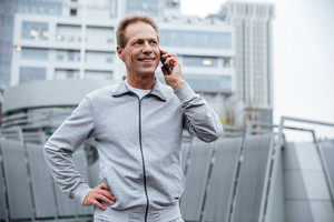 Smiling Runner in gray sportswear talking at phone with arm at hip and standing on the street