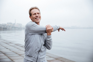 Smiling Runner in gray sportswear warming up near the water
