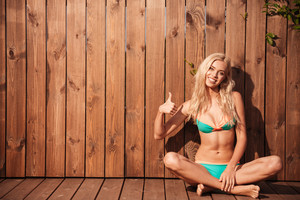 Smiling sexy blonde woman in bikini sitting and showing thumb up over wooden background