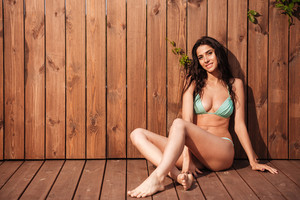 Smiling sexy woman in bikini sitting over wooden background and looking at camera