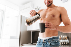 Smiling shirtless young man standing and pouring coffee into the cup on the kitchen