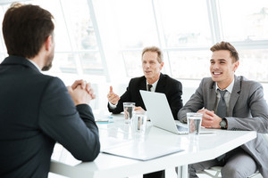 Smiling smart business people working on difficult financial project in office