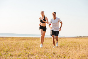 Smiling sports couple running together outdoors