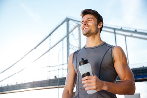 Smiling sports man resting after running and holding water bottle