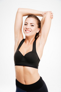 Smiling sports woman stretching hands over white background