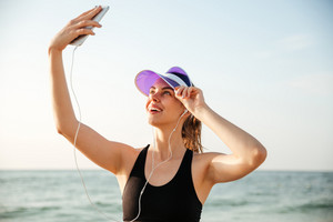 Smiling sporty young woman taking selfie using smartphone on beach
