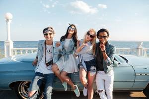 Smiling stylish young friends standing and sending kiss near cabriolet