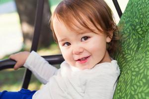 Smiling toddler girl swinging on a swing