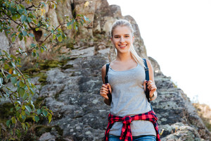 Smiling traveling girl with backpack on rock looking at camera