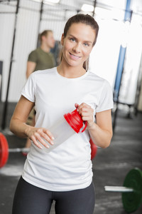 Smiling woman at fitness gym taking a break