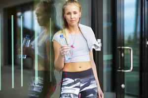 Smiling woman drinks water after workout in the city