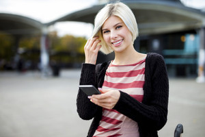 Smiling Woman Holding Mobile Phone Outside Railroad Station
