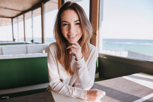 Smiling Woman in cafe near the sea looking at camera