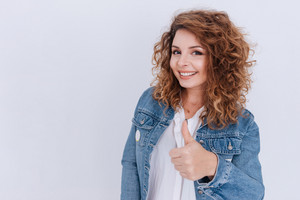 Smiling Woman in jean jacket showing thumb up and looking at camera over gray background