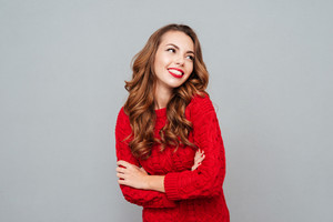 Smiling woman in red sweater looking away over gray background